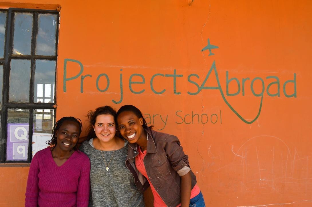 En volontär poserar utanför med personal från en skola som Projects Abroad byggt.